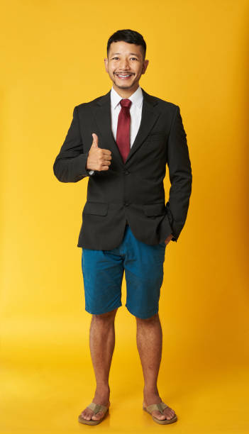 Happy asian man in flip flops Happy asian man in flip flops with thumb up isolated on yellow background shorts stock pictures, royalty-free photos & images