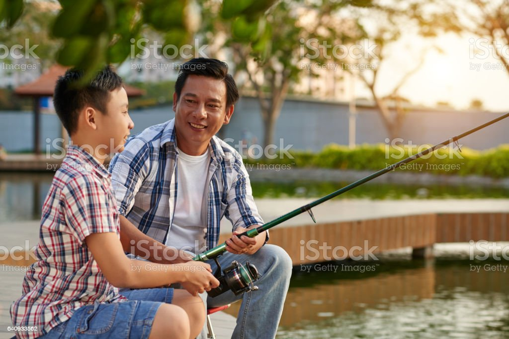 Happy Asian man spending weekend with his son stock photo