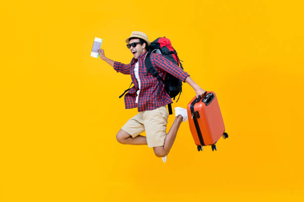 Happy Asian man with air ticket jumping stock photo