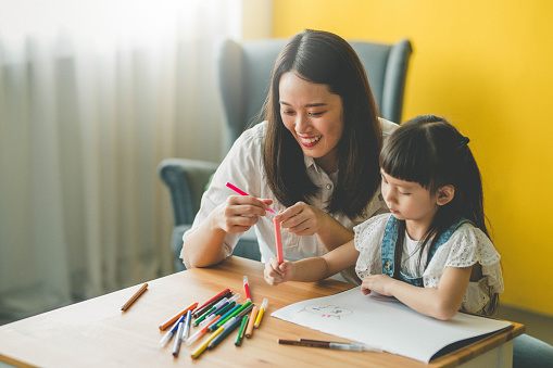Image of Happy Asian Mother and daughter drawing together at living room.