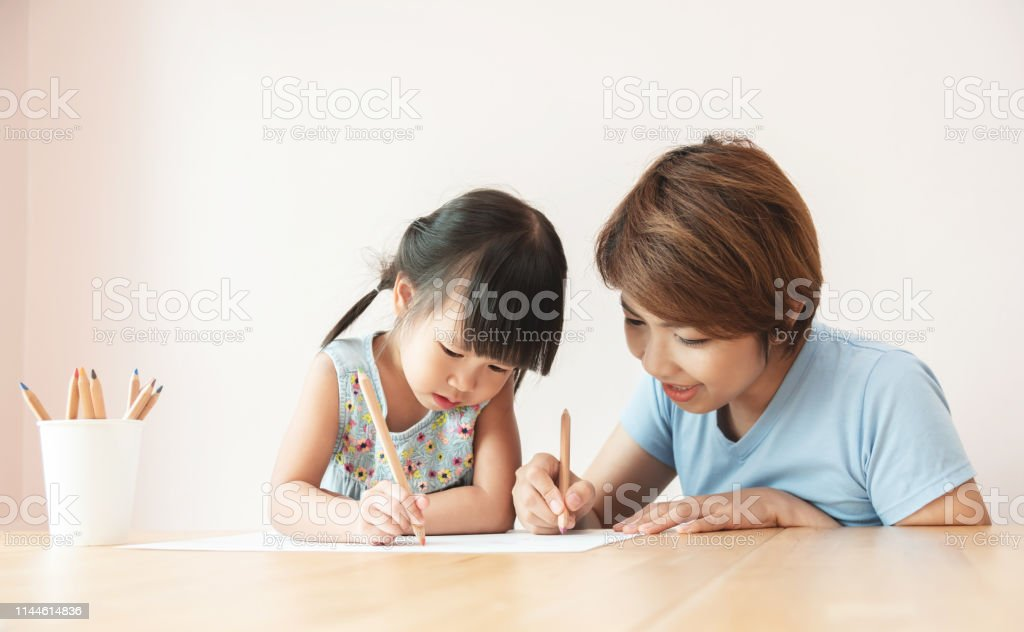 Happy Asian Mother and daughter drawing together. - Foto stock royalty-free di Adolescente
