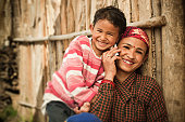 Outdoor day time image of mature Nepalese women attending a phone call while her daughter trying to listen by putting her ear on phone at the same time and leaning over the shoulder of her mother. They are sitting with the wall of their traditional wooden hut. Two people, waist up, horizontal composition with copy space.