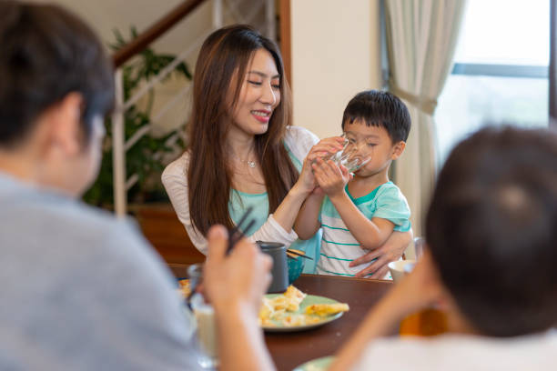Happy Asian Mother Helping Her Young Son With Breakfast stock photo