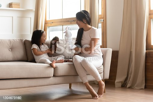 Happy Asian young mom sit on couch playing with cute little ethnic daughter in living room, overjoyed Vietnamese millennial mother or nanny have fun engaged in funny game with small girl child