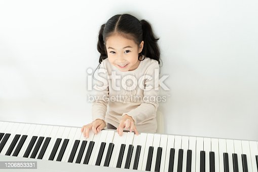 From above of positive smiling adorable Asian girl practicing music playing piano relaxing in house looking at camera