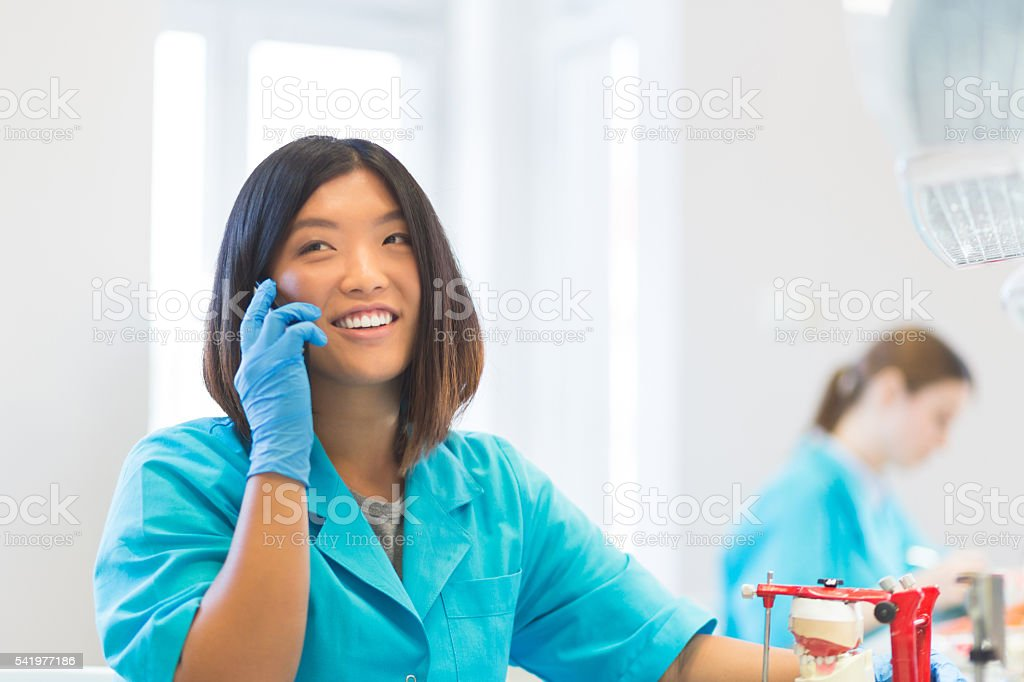 Happy asian prosthetic dentistry student talking on phone stock photo