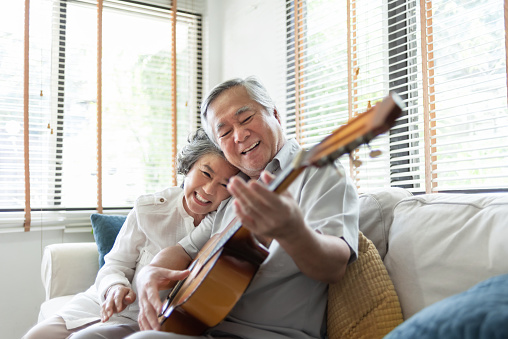 Happy Asian senior Couple enjoying singing and playing acoustic guitar together on sofa at home. Joyful Grandfather and Grandmother celebrating their Wedding Anniversary.