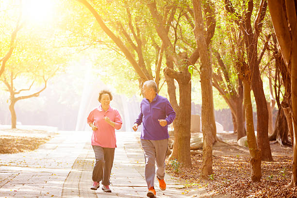 happy asian Senior Couple Exercising In the Park stock photo