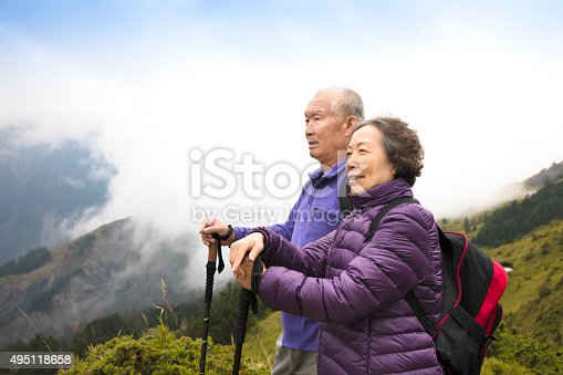 istock happy asian senior couple hiking on the mountain 495118658
