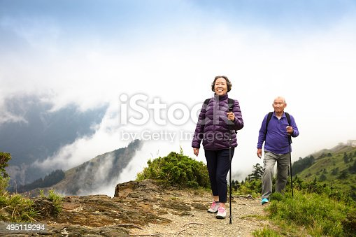 istock happy asian senior couple hiking on the mountain 495119294