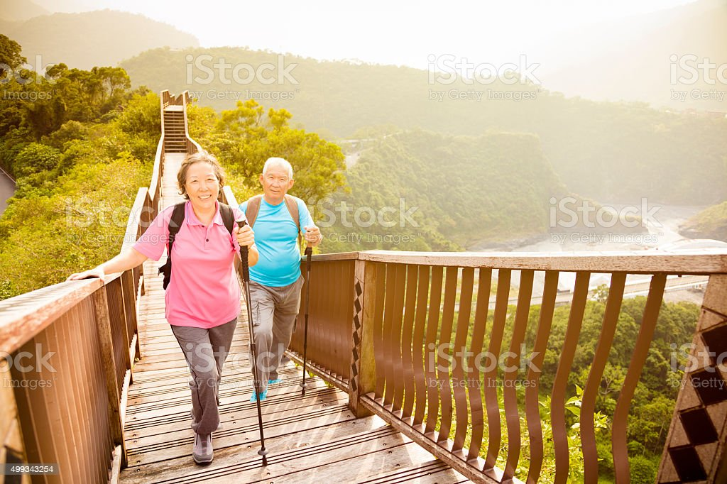 happy  asian senior couple hiking on the mountain stock photo