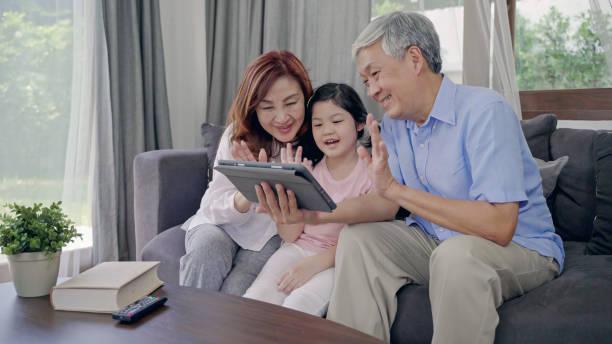 Feliz asiático Senior Pareja estilo de vida y familia,Abuelos con su grandaughte Videoconferencia por tableta - foto de stock