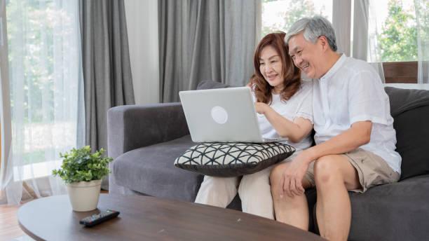 Concepto de dispositivo de la tecnología de estilo de vida asiático feliz Senior couple, encantadora pareja de ancianos con computadora portátil - foto de stock