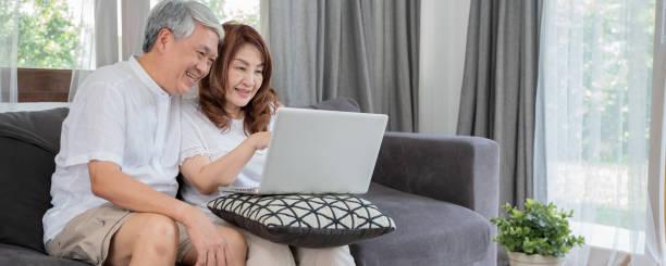 Feliz asiático Senior Pareja concepto de dispositivo de tecnología de estilo de vida,Lovely pareja de ancianos usando computadora portátil en la sala de estar - foto de stock