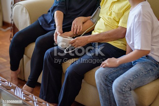 Image of Happy Asian Senior couple taking blood pressure with grandson in living room.