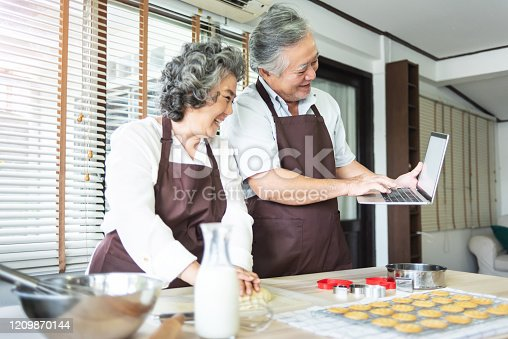 istock Happy Asian senior couple using laptop computer for online cookies class while preparing dough together. 1209870144