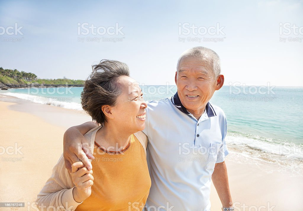 happy asian seniors walking on the beach stock photo
