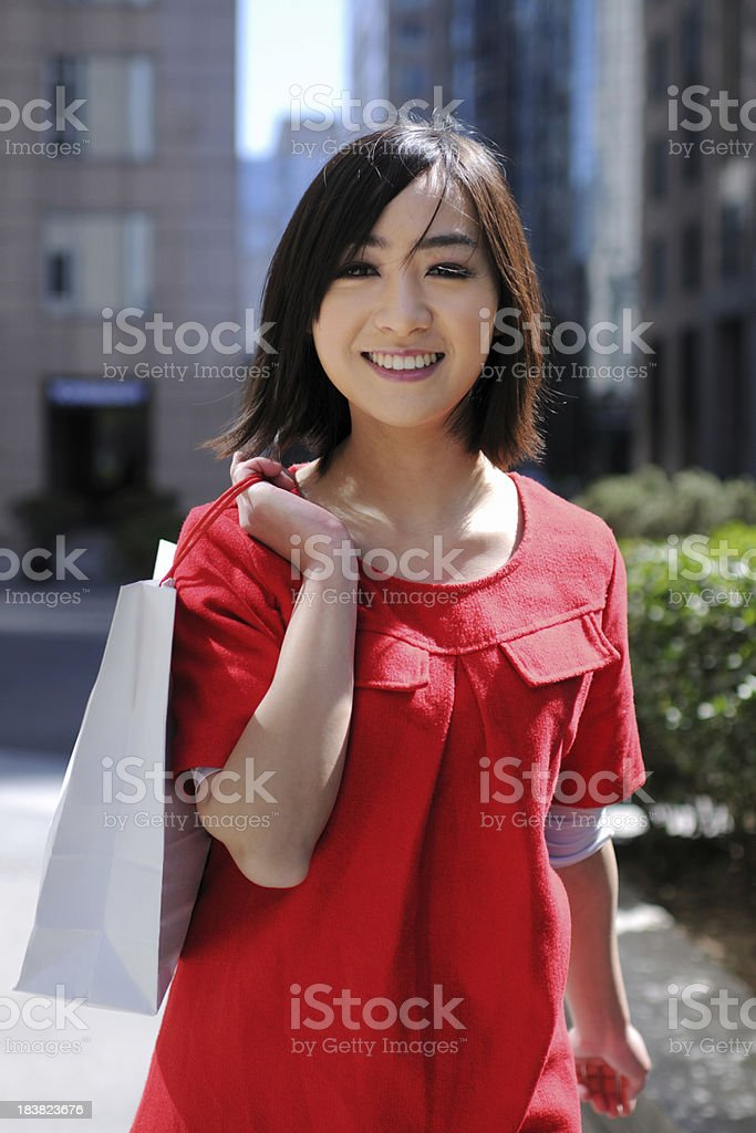 A happy asian woman shopping with shopping center background
