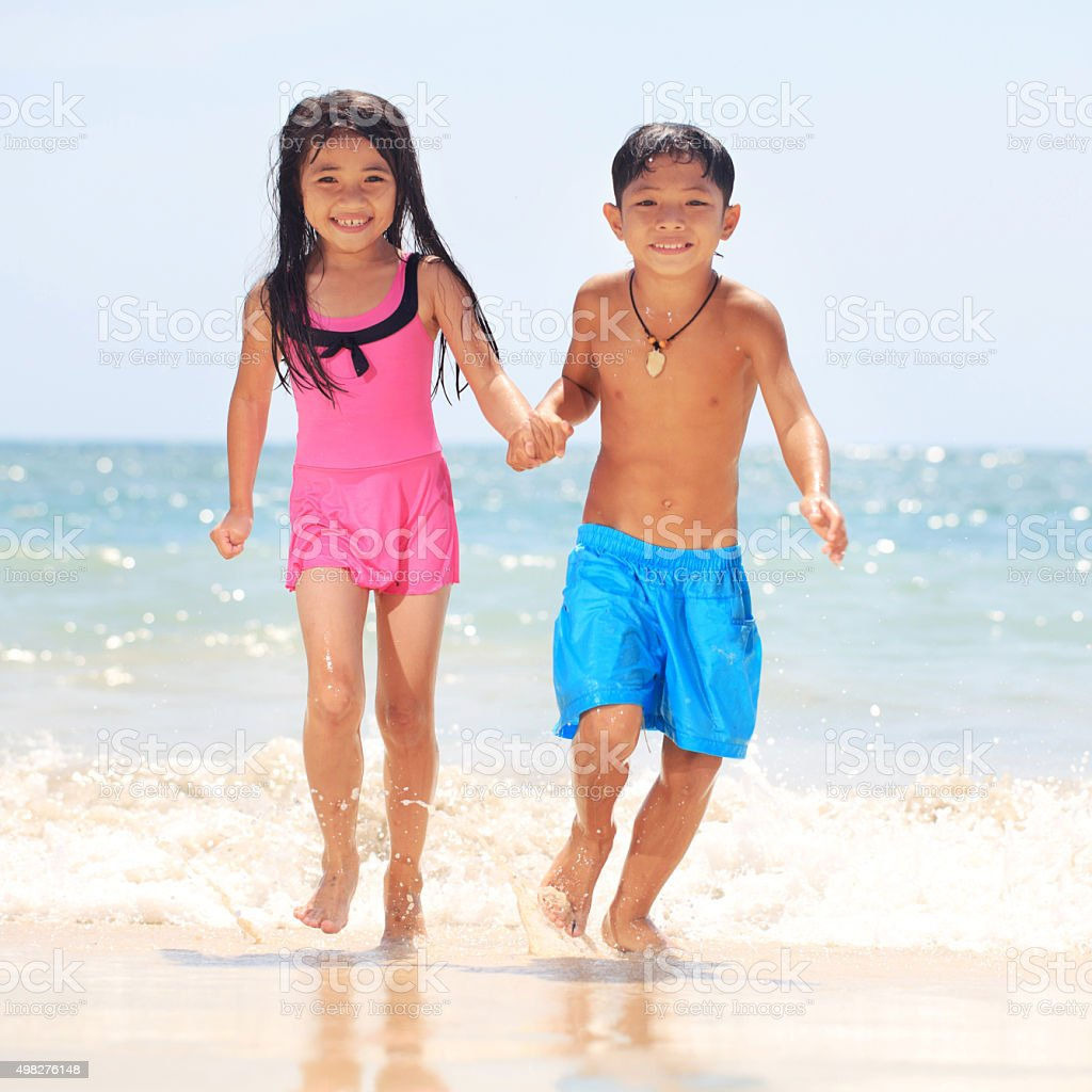 Happy Asian siblings running at beach and looking at camera. stock photo