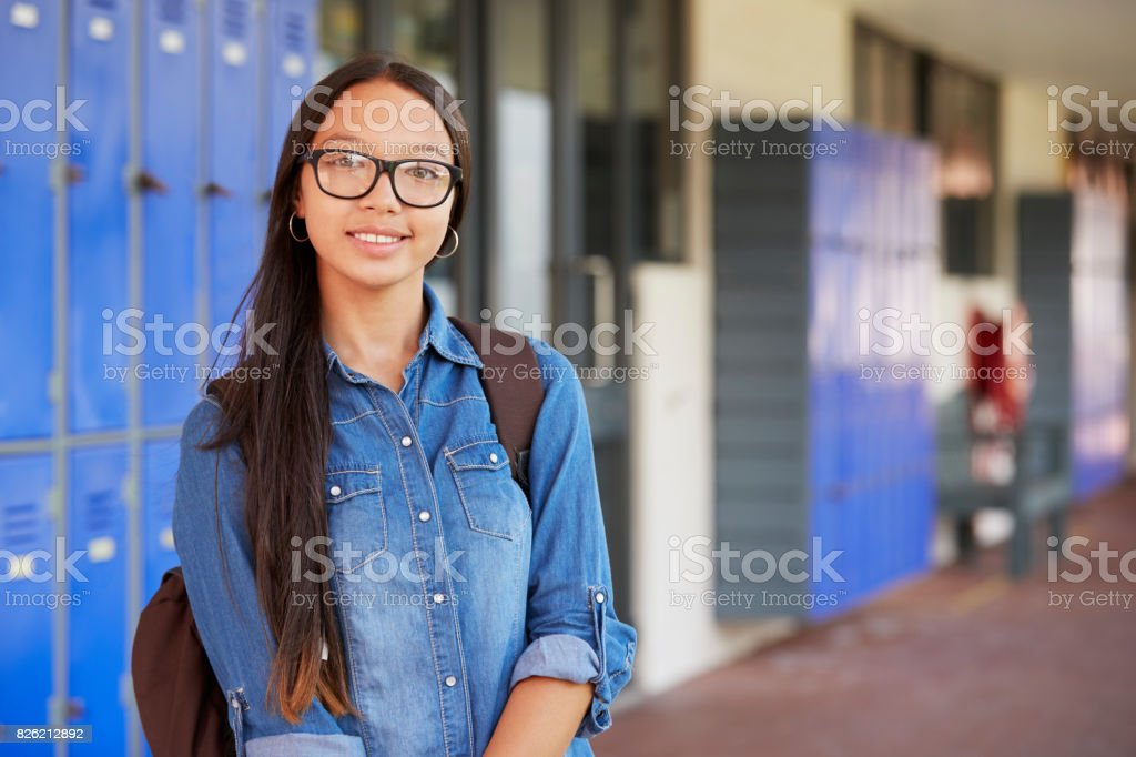 Happy Asian teenage girl smiling in high school corridor stock photo