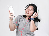 istock Happy Asian teenager girl using headphone and listening music. 1064157328