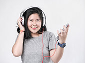 istock Happy Asian teenager girl using headphone and listening music. 1064451862
