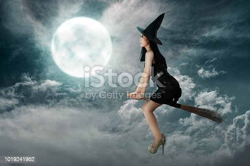 istock Happy asian witch woman flying above a broomstick 1019241952