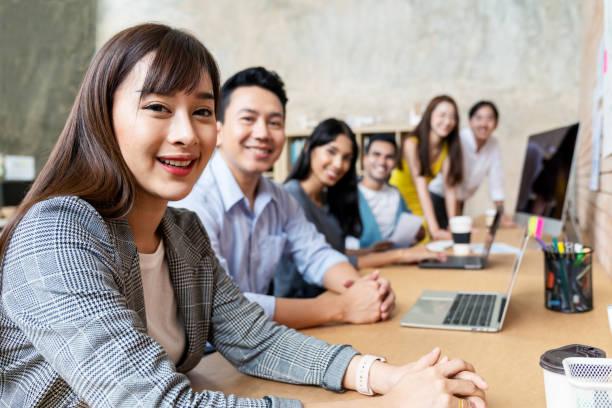 glückliche asiatische frau und kreatives team lächeln und schauen in die kamera in modernen arbeitsbereich büro. glückliche gruppe von selbstbewussten mitarbeiter in der koarbeit. beziehungs- und engagementkonzept. - mitarbeiterengagement stock-fotos und bilder