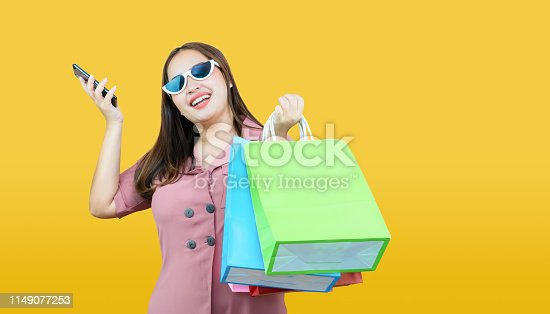 861940002 istock photo Happy asian woman casual clothes holding credit card and shopping bags on light yellow background. 1149077253