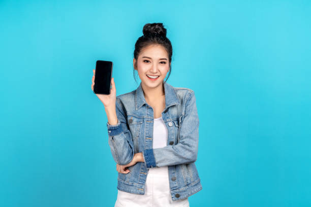 Happy asian woman feeling happiness and standing hold smartphone on blue background. Cute asia girl smiling wearing casual jeans shirt and connect internet shopping online and present stock photo