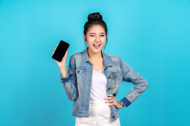 Happy asian woman feeling happiness, blinks eyes and standing hold smartphone on blue background. Cute asia girl smiling wearing casual jeans shirt and connect internet shopping online and present stock photo
