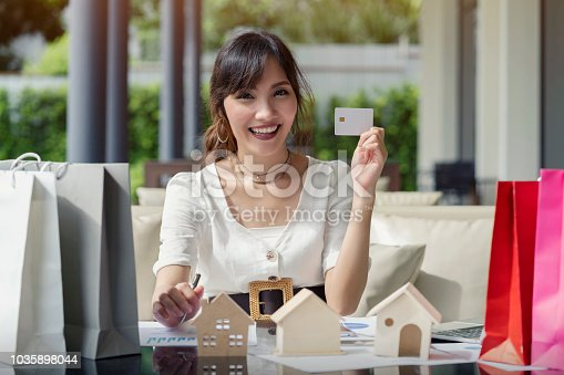 Happy asian woman holding white credit card mockup payment for online shopping, represent sale homes real estate purchase.