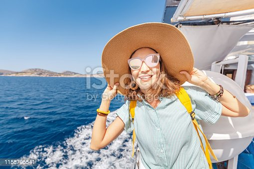 Happy asian woman in hat enjoying travel and vacation on Cruise ship. Tourist girl on the deck