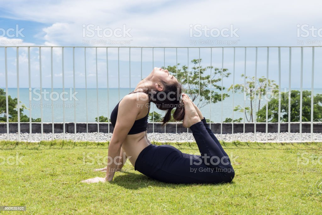 Happy Asian Woman Practice Yoga King Cobra Or Raja Bhudjangasana Pose To Stretching Her Muscle With