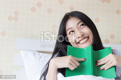 1176252245 istock photo Happy Asian woman reading a book on bed. 831525334