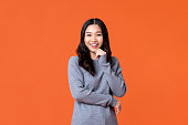Young happy Asian woman smiling with hand on chin isolated on orange studio background