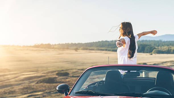 feliz mulher asiática de pé em cabriolet com os braços levantados - viagem aos estados unidos - fotografias e filmes do acervo
