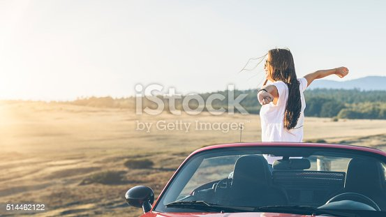 istock happy asian woman standing in  cabriolet with arms raised 514462122