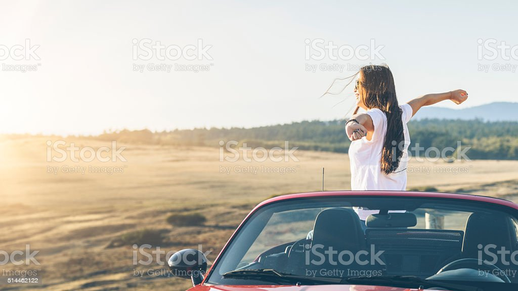happy asian woman standing in  cabriolet with arms raised stock photo