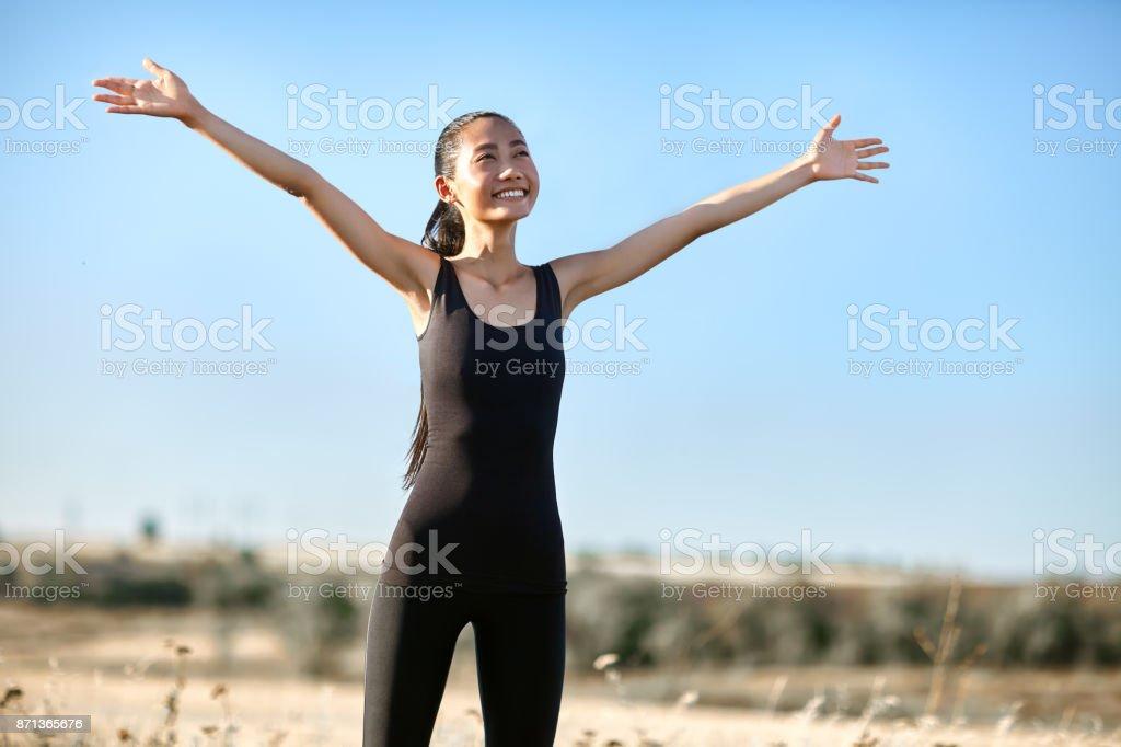 Glücklich asiatische Frau stehend mit offenen Armen entgegen der Sonne – Foto