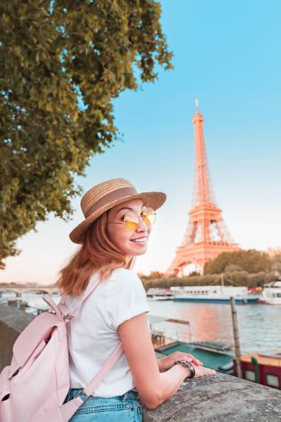 Glückliche asiatische Studentin mit Rucksack mit Blick auf den Eiffelturm in Paris. Konzept für Reisen und Bildung in Frankreich – Foto