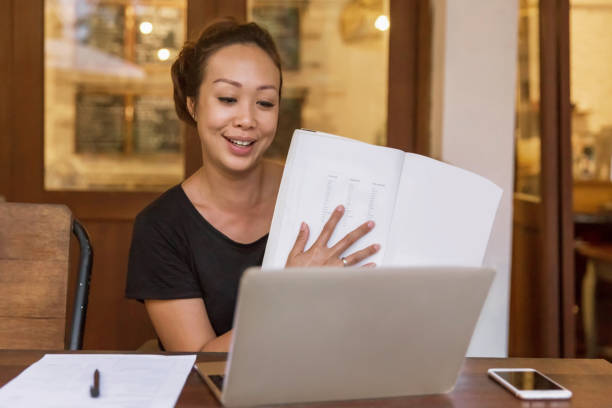 Happy Asian woman teaching online class from home during Covid 19 pandemic stock photo