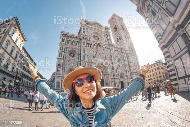 Happy asian woman tourist with raised hands at the old town square of picture id1144972085?b=1&k=6&m=1144972085&s=612x612&h=gikkbhhhtjnepdhh2 stodwg5incbe4cfvv9bhrv5lk=