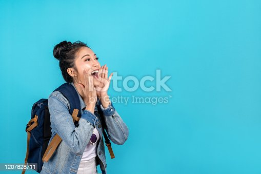 Happy asian woman travel backpacker shouting open mouth to copyspace on blue background. Cute asia girl smiling wearing casual jeans shirt and looking to aside for present promotions.