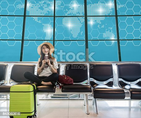 istock Happy Asian woman traveler holding the passport with suitcases and waiting for airplane arrive in modern an airport with Network graphic world map background, travel and transportation concept. 843060816
