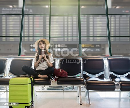 istock Happy Asian woman traveler holding the passport with suitcases and waiting for airplane arrive in modern an airport with travel information board background, travel and transportation concept. 843060818