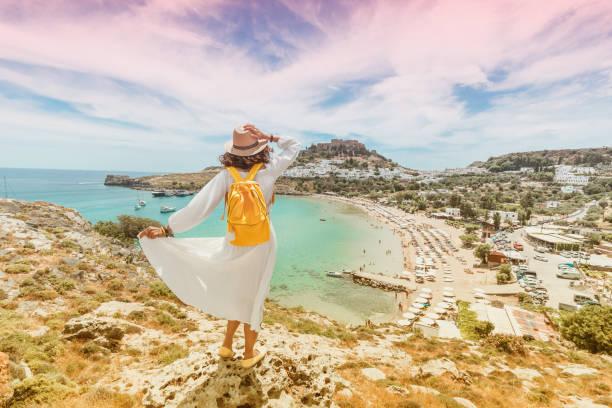 Glückliche asiatische Frau reist in Griechenland. Spaß bei der atemberaubenden Aussicht auf das Meer Resort und die Altstadt von Lindos auf dem Berg – Foto