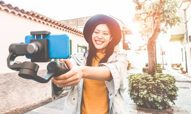 happy asian woman vlogging with gimbal tripod and smartphone - influencer chinese girl having fun with new trend technology - millennial generation activity job, youth and tech concept - focus on face - photo messaging stock photos and pictures