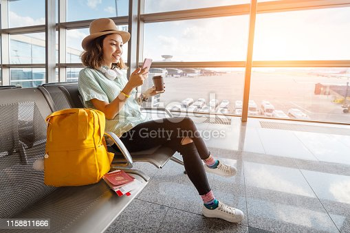 Happy asian woman waiting for her airplane in airport with passport and baggage. Vacation and journey concept