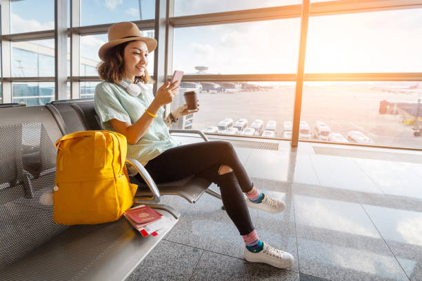 Happy asian woman waiting for her airplane in airport with passport and baggage. Vacation and journey concept Happy asian woman waiting for her airplane in airport with passport and baggage. Vacation and journey concept passenger stock pictures, royalty-free photos & images